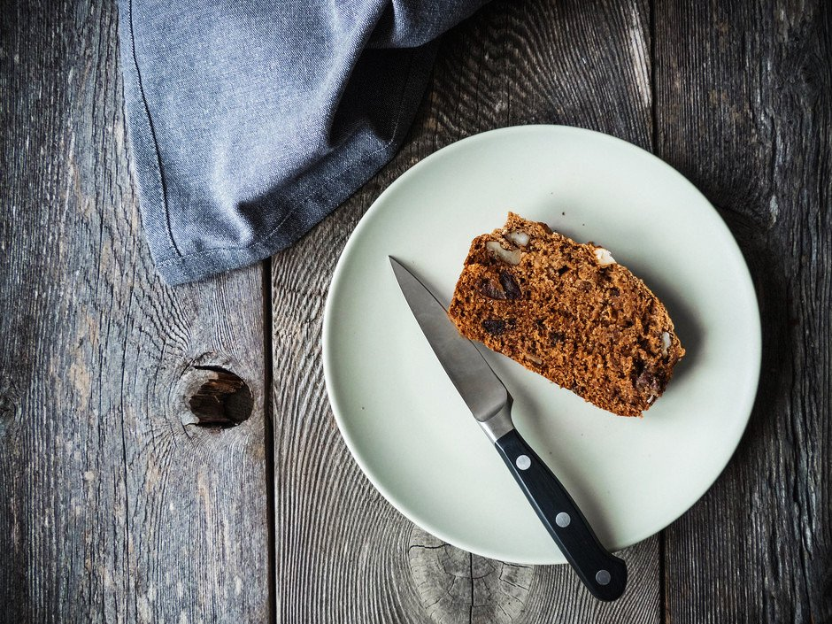 A slice of rosemary bread on a  white plate with a knife on a wood surface with a blue linen.