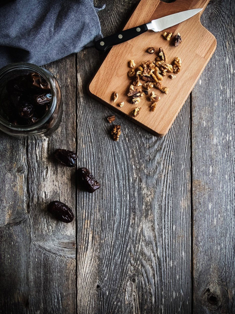 an over head image of walnuts on a cutting board with a knife, and dates in a jar on a wood surface.