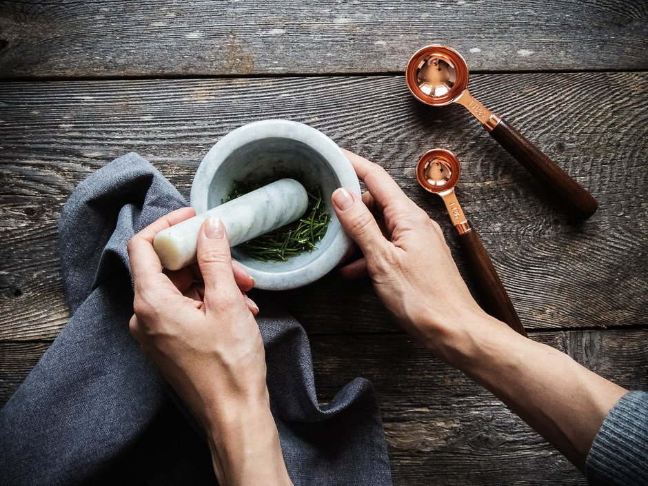 overhead image of a persons hands grinding rosemary in a mortar and pestel with a blue linen and two copper teaspoons on the side.
