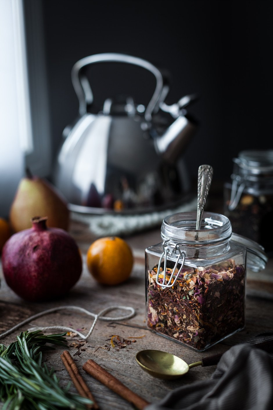 closeup image of a homemade tea blend in a glass jar with a kettle in the background..
