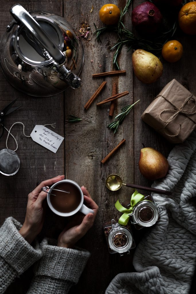 overhead image of a tea kettle, winter fruits, and hands holding a cup of freshly brewed tea.