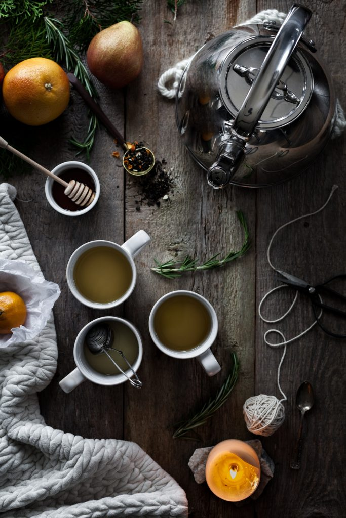 overhead image of three mugs of tea with a candle, oranges and a ball of string.