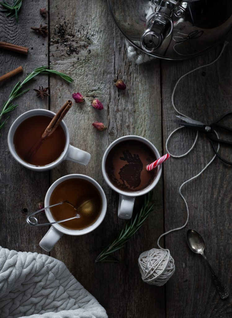 overhead image of three mugs of tea sitting next to a kettle with a ball of string.