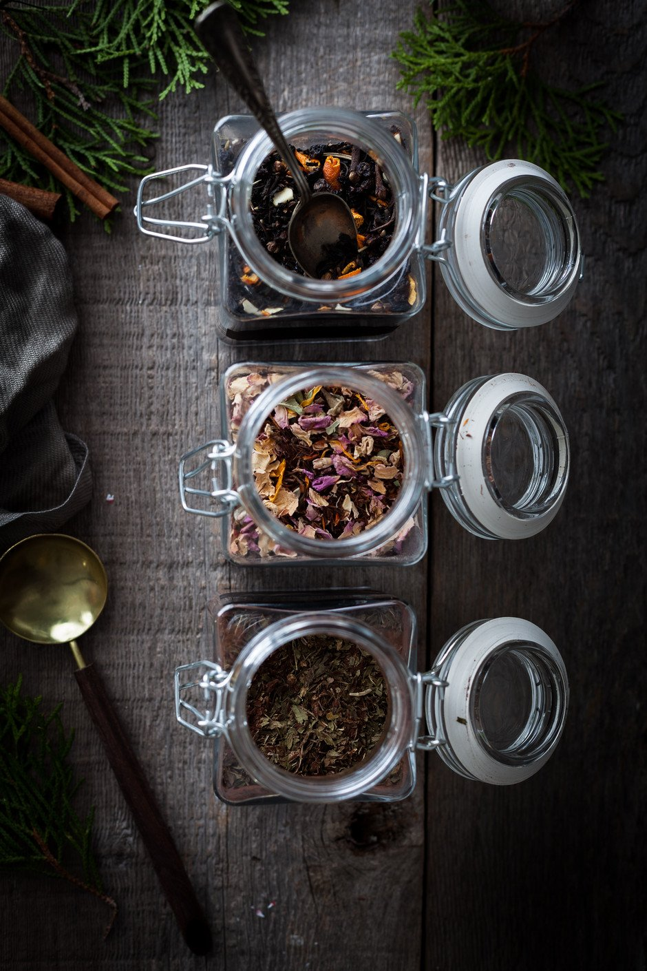 overhead image of tea blends in jars on a wooden surface.