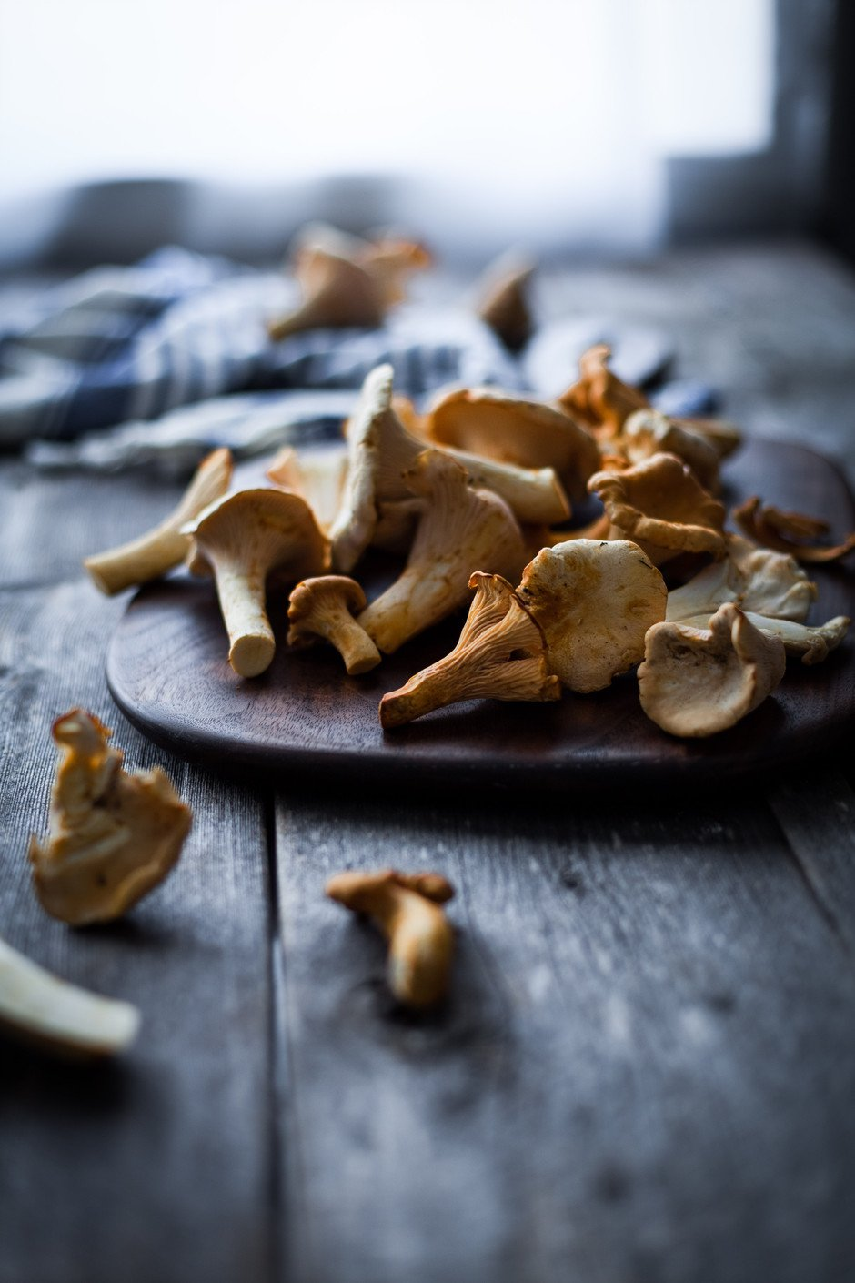 Chanterelle mushrooms on wood cutting board.