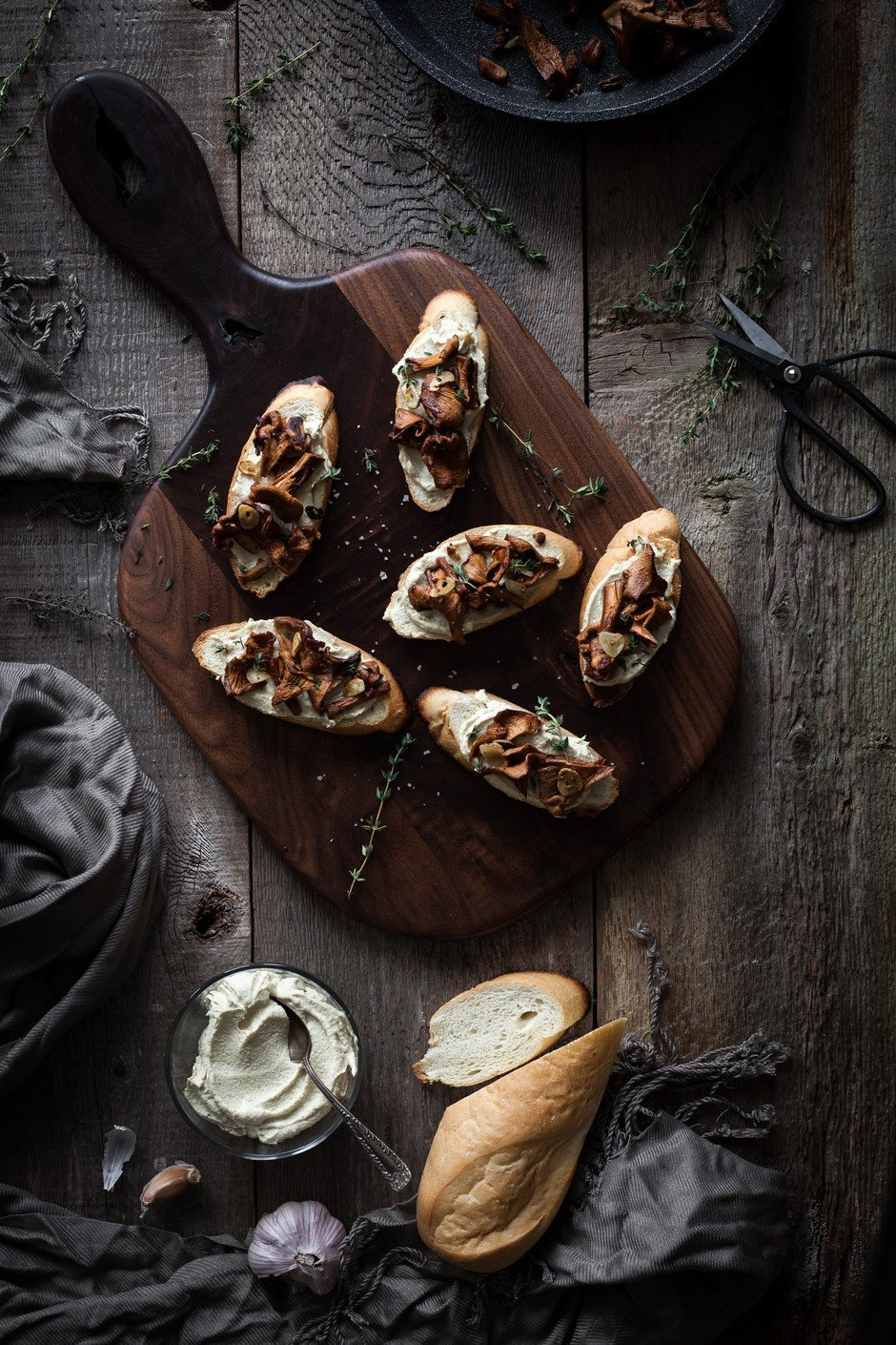 overhead portrait of chanterelle crostinis on a cutting board with herbs and french bread.