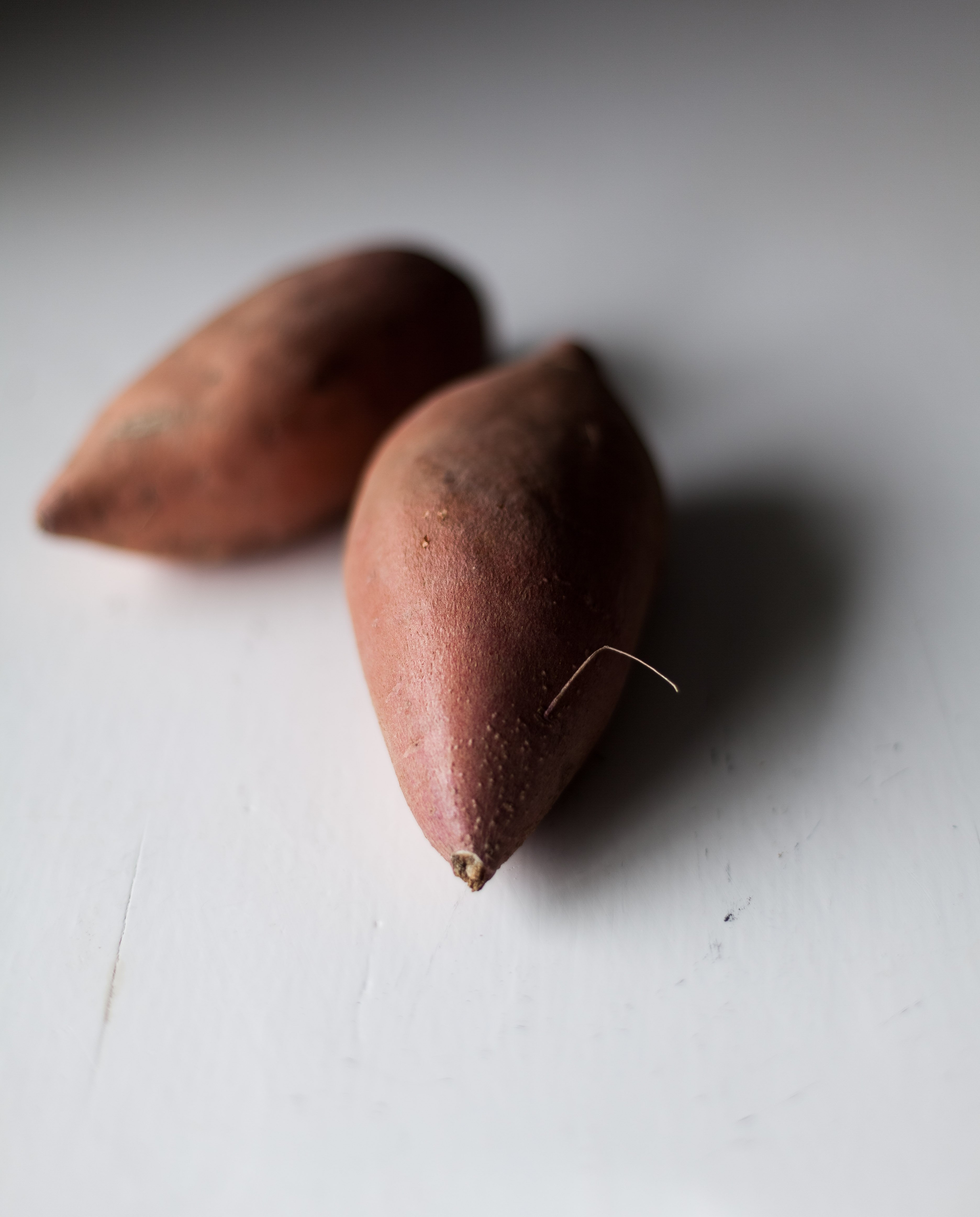 a closeup image of two sweet potatoes on a white surface.