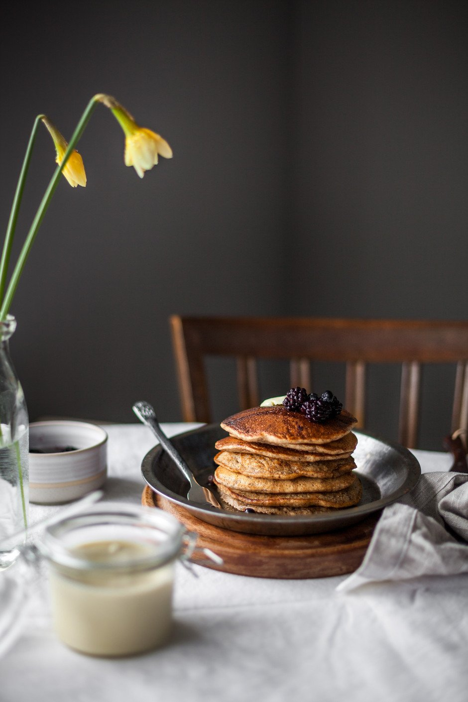 A head on image of a stack of pancakes on a pie plate on a breakfast table with a vase of flowers.