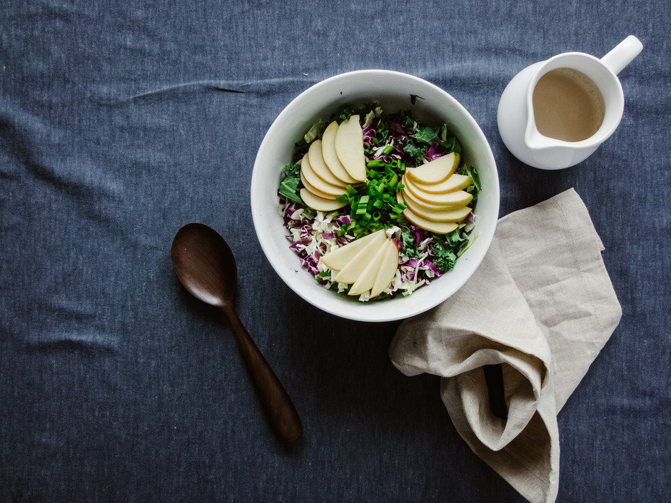 overhead of a bowl of kale slaw with a wooden spoon, beige linen and jar of dressing on the side.