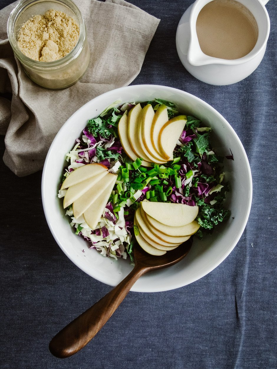 overhead image of kale slaw topped with apples and green onions with a beige linen, dressing and Parmesan on the side.