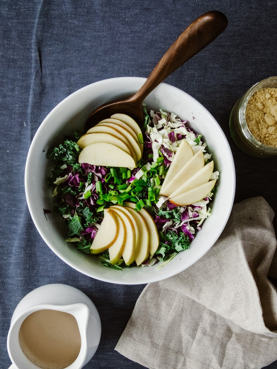 overhead image of kale slaw topped with apples and green onions with a beige linen on the side.