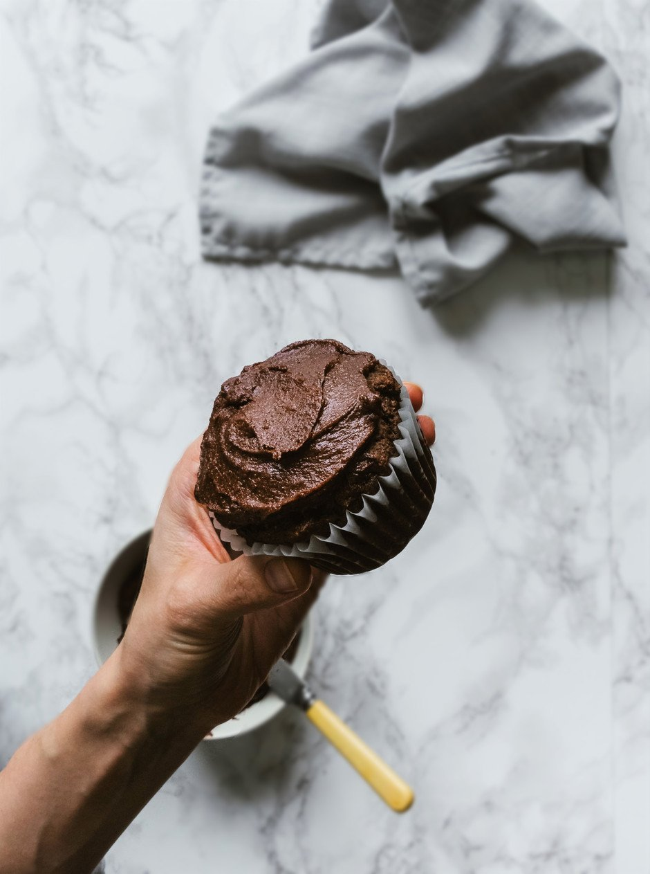 overhead closeup of a hand holding a frosted chocolate cupcake against a white marble surface,