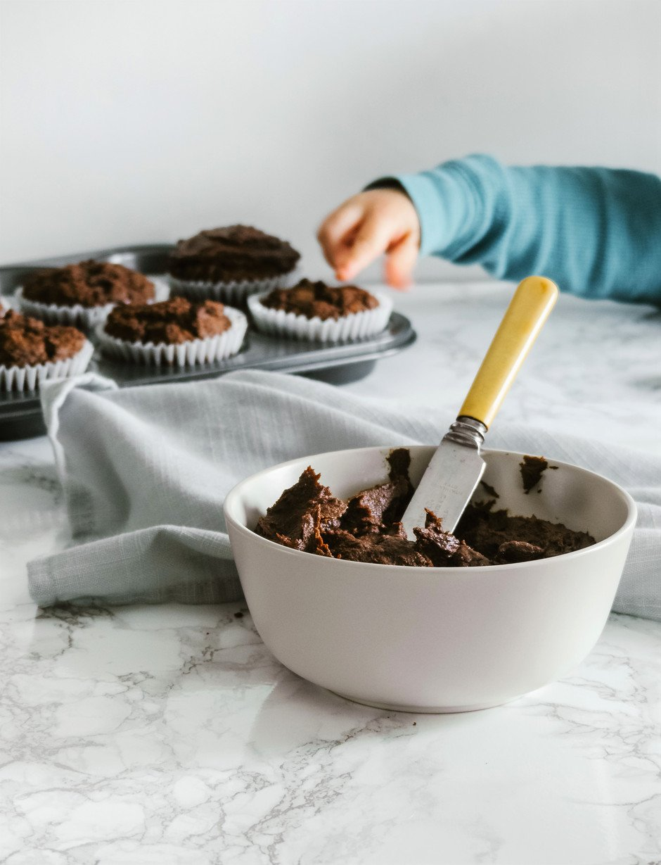 close up portrait of a white bowl of chocolate frosting sitting on a marble surface with cupcake in the background a child's hand reaching for one.