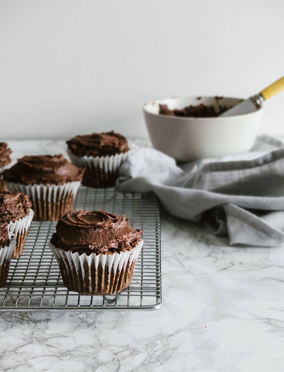a portrait of frosted vegan triple chocolate cupcakes on a wire rack with a blue linen and a white bowl of frosting in the background.