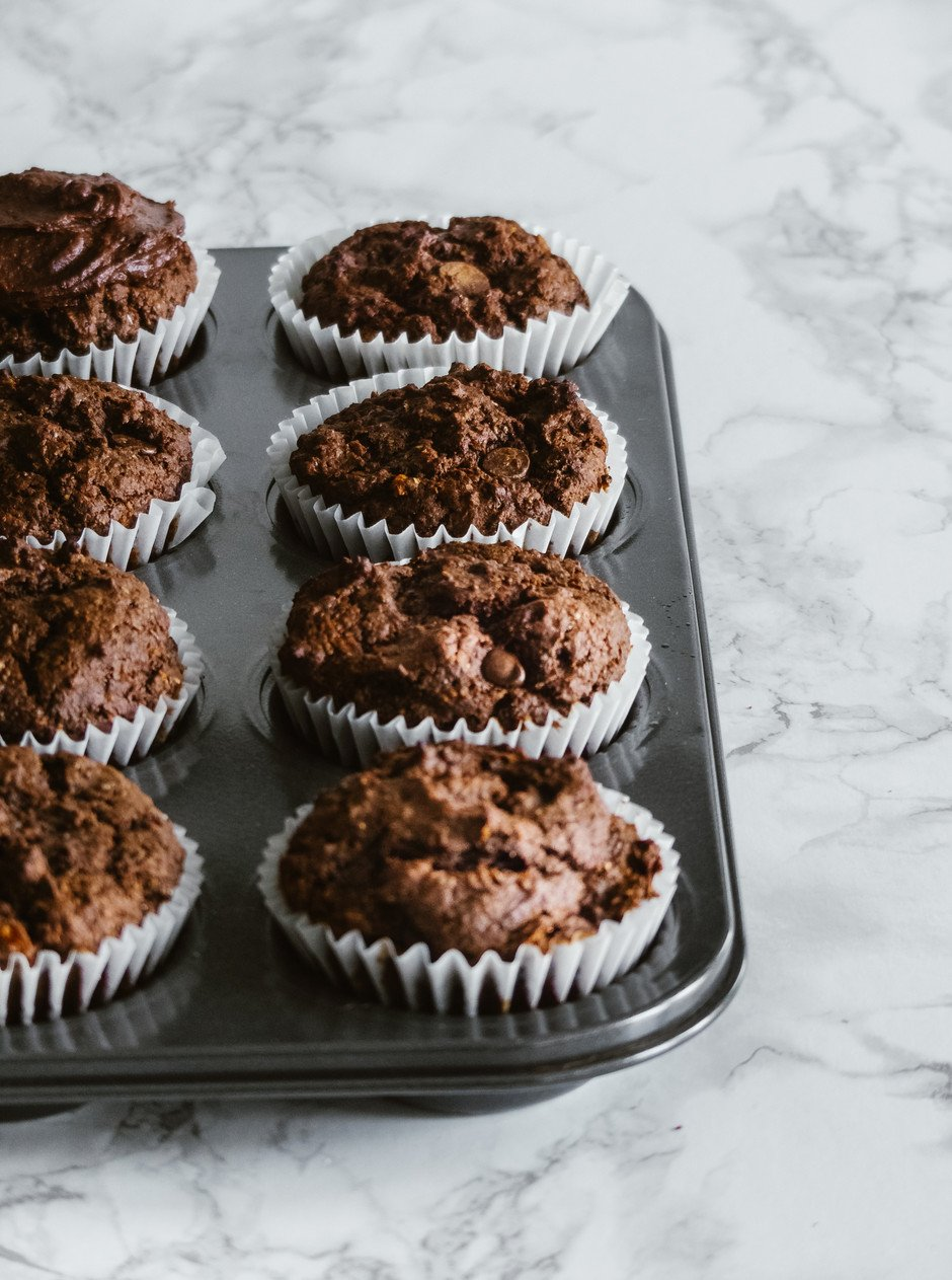 angled close up portrait of chocolate cupcakes in a muffin tin on a white marble surface.