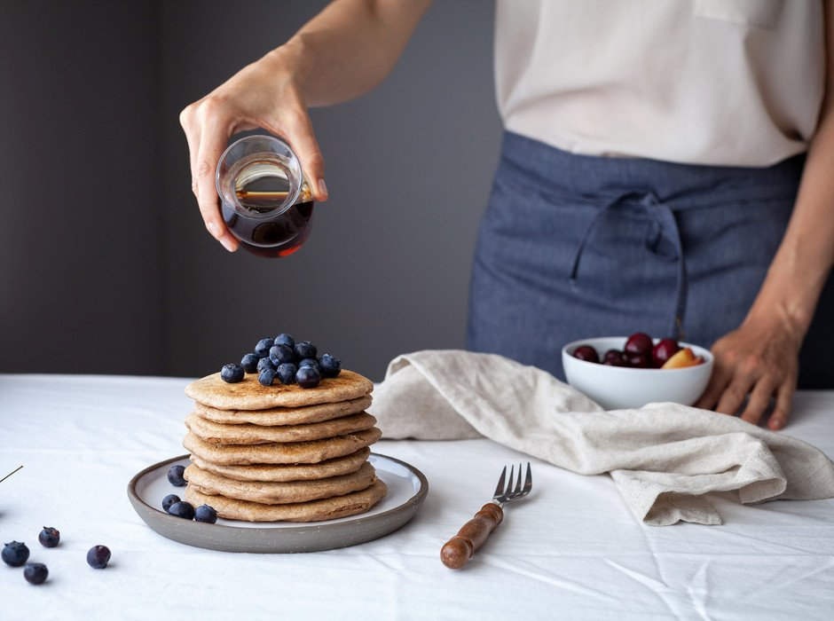 A baker about to pour maple syrup over a stack of fluffy vegan spelt pancakes.