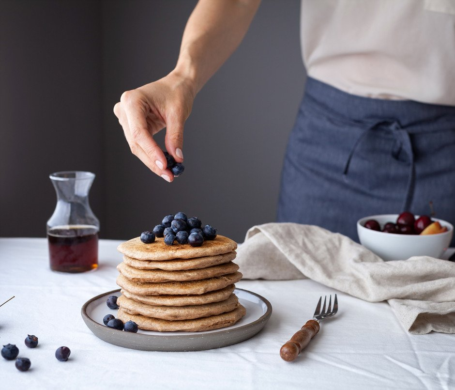 a baker placing blueberries on top of a stack of fluffy vegan spelt pancakes.
