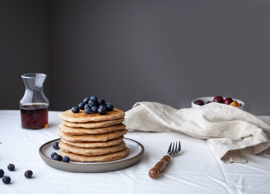 a stack of vegan spelt pancakes with blueberries on top.