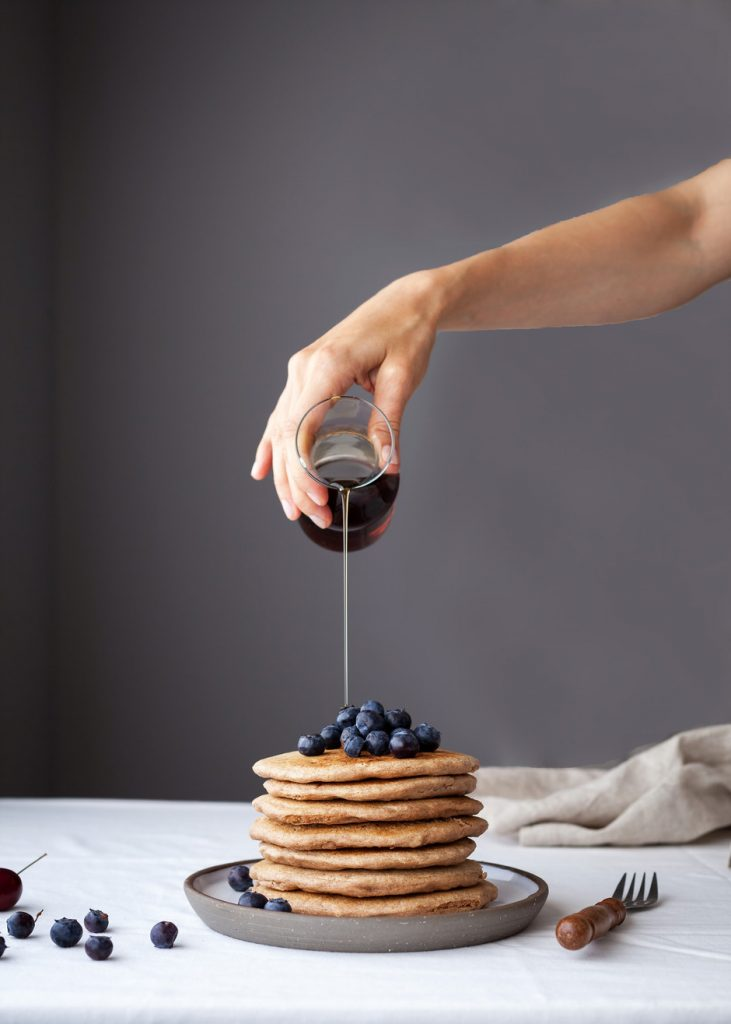 head on image of a stack of pancakes with blueberries ontop with maple syrup being poured on top.