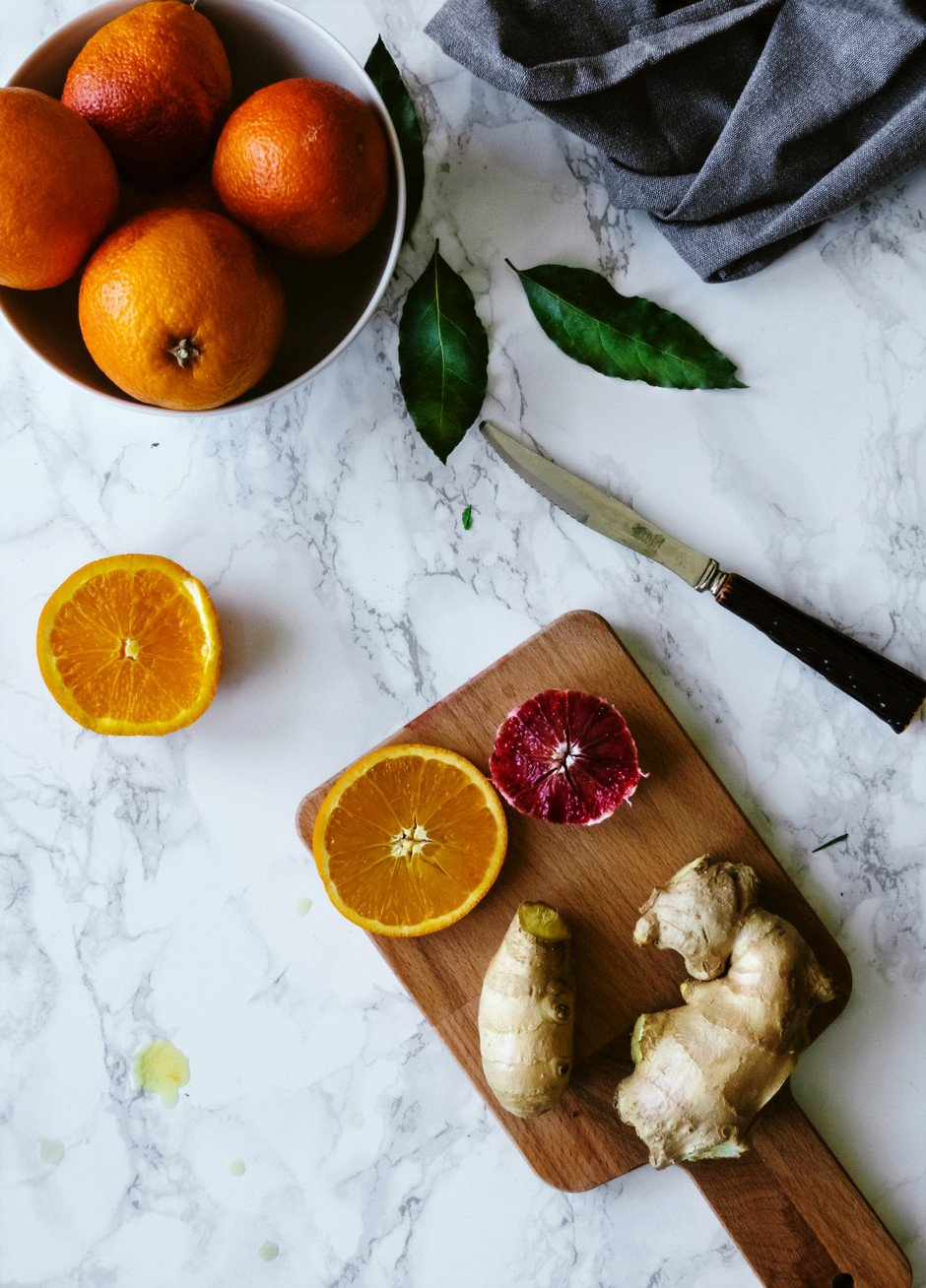 an overhead image of a cutting board with citrus slices, ginger and a knife.