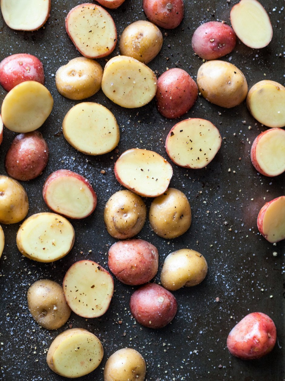 overhead view of sliced potatoes on a baking sheet.