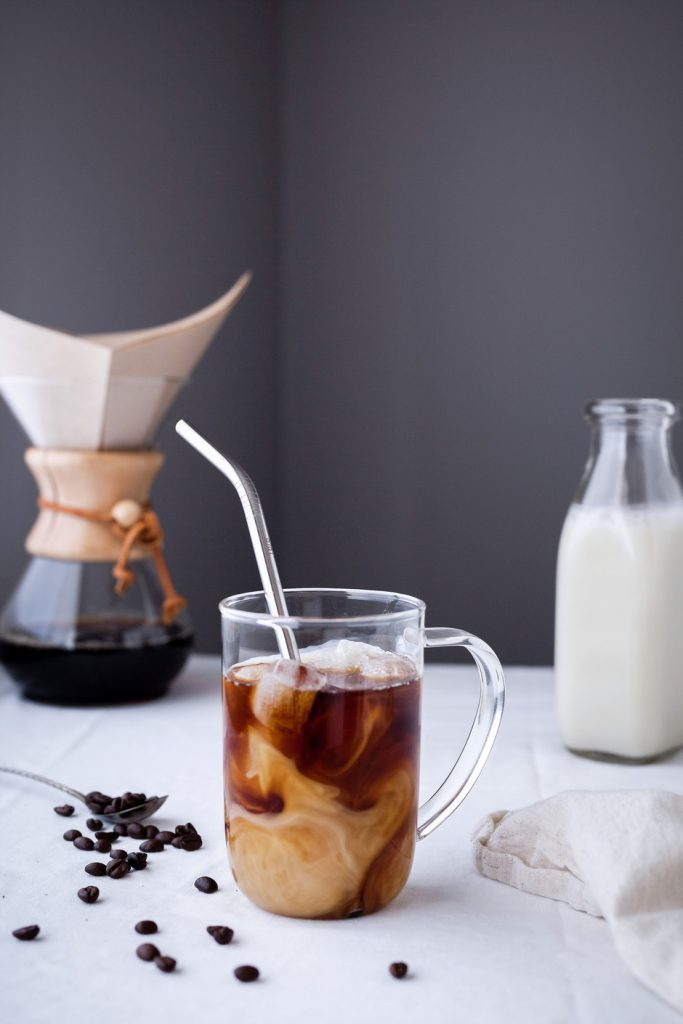 a head on image of a cup of cold brew coffee with a chemex coffee maker in the background with a jug of almond milk.