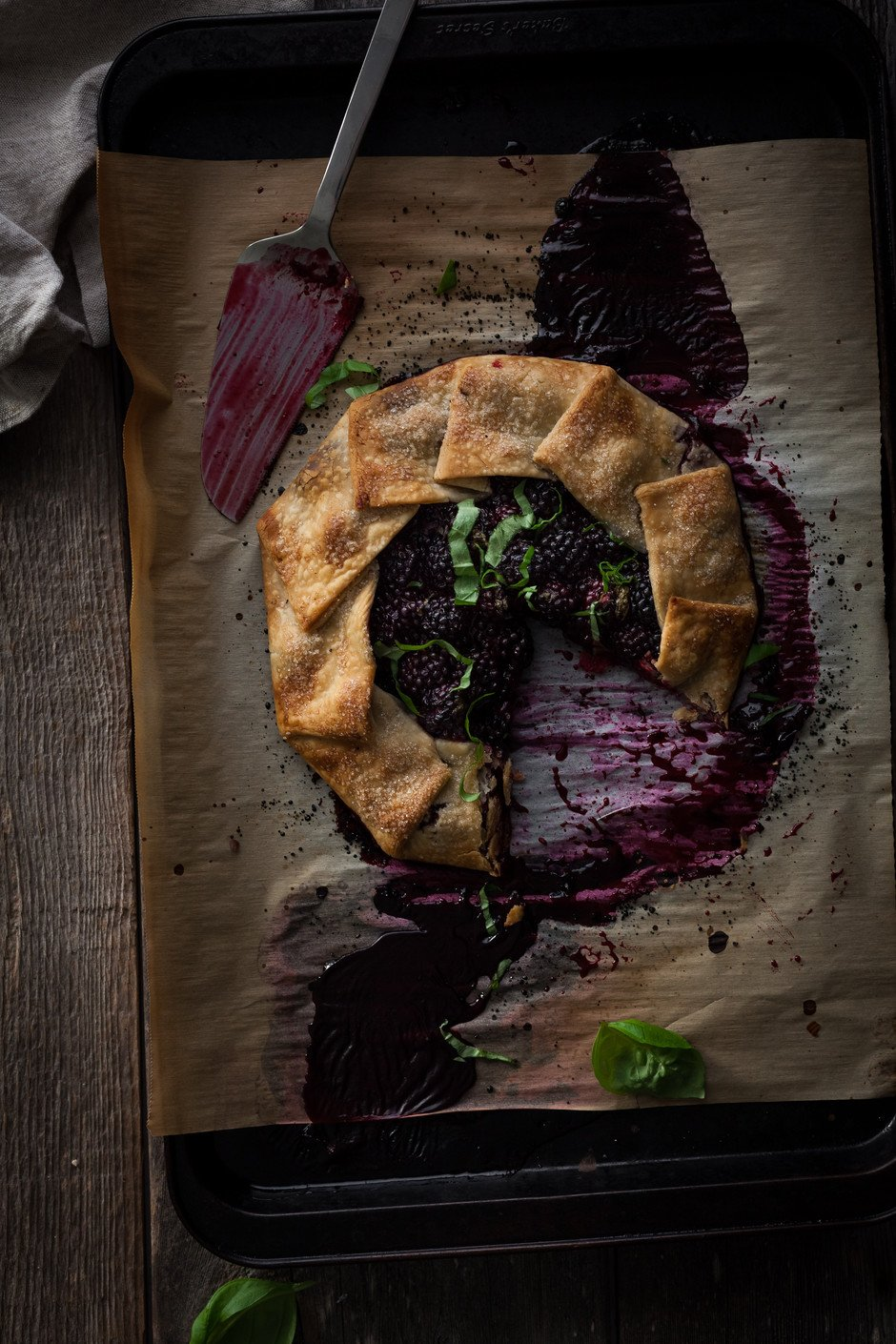 overhead of a blackberry galette on a baking tray with a slice missing and a cake server.