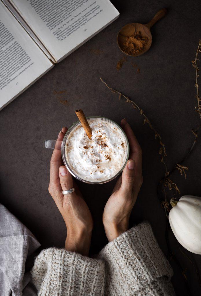 hand cupping pumpkin spice latte.