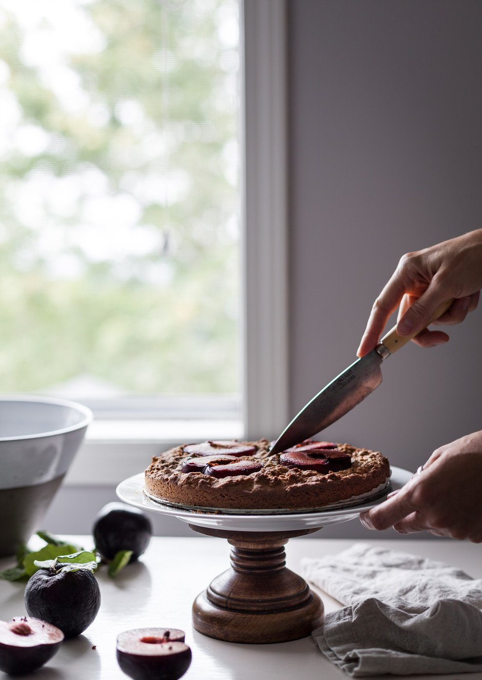 portrait of a hand holding a knife cutting a cake on a cake stand.