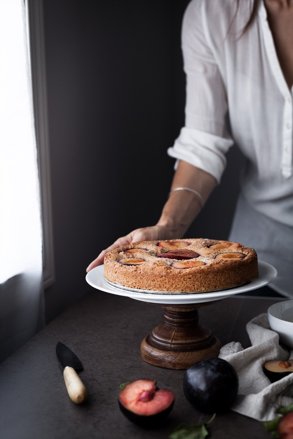 portrait of a person holding a plum cake on a cake stand.