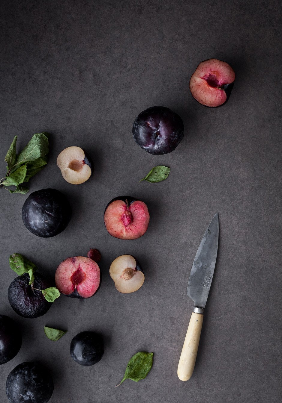 overhead view of sliced plums and leaves and a knife.