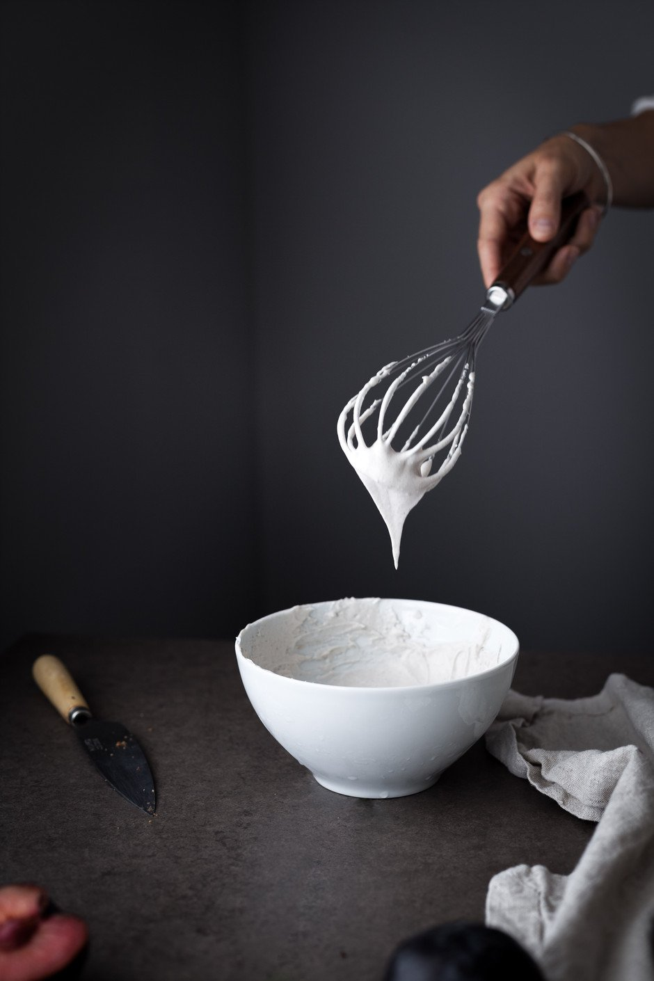 a hand holding a whisk with coconut cream dripping off it.