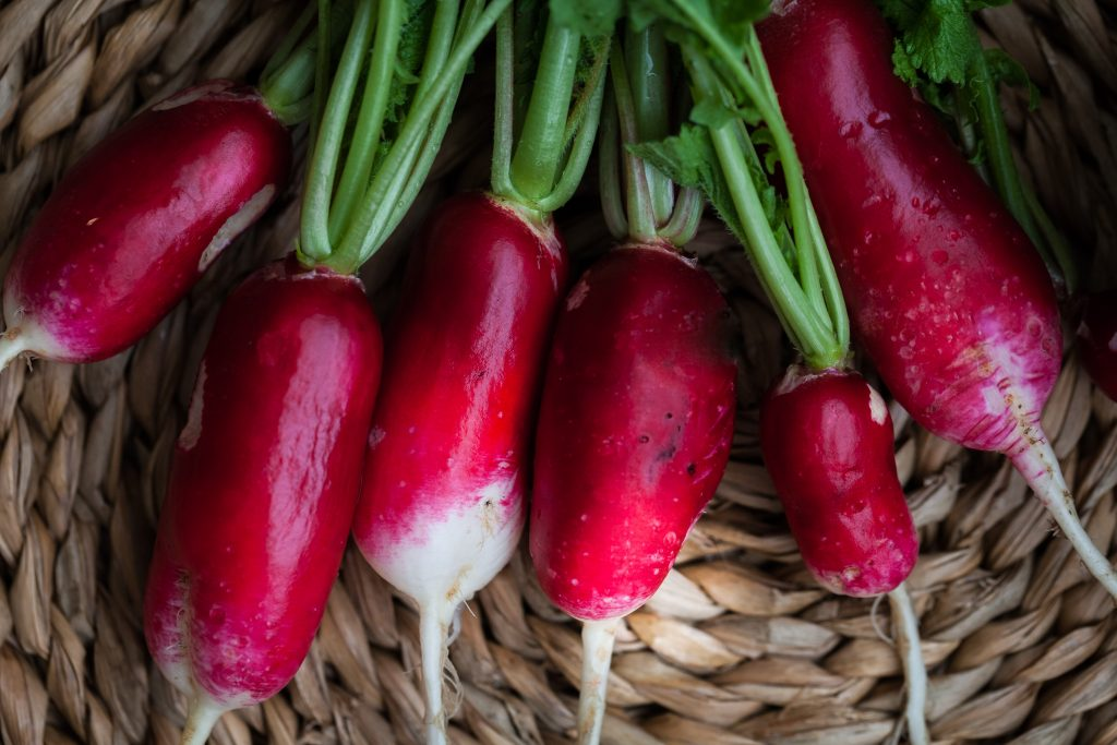 overhead closeup image of 6 fresh radishes in a basket.