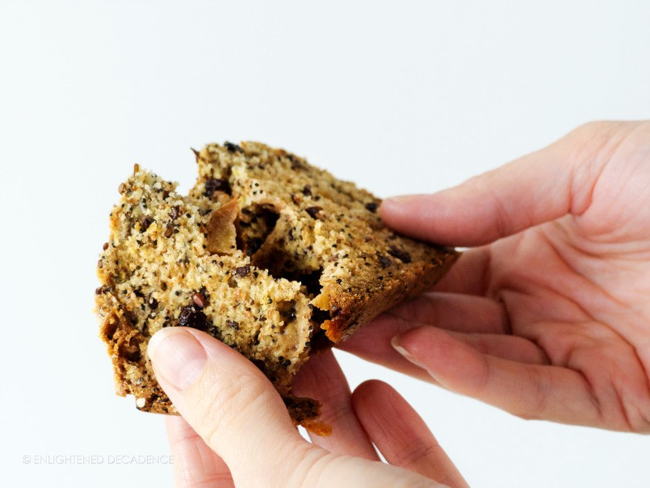 A person holding a slice of harvest apple crunch loaf and breaking it in half.