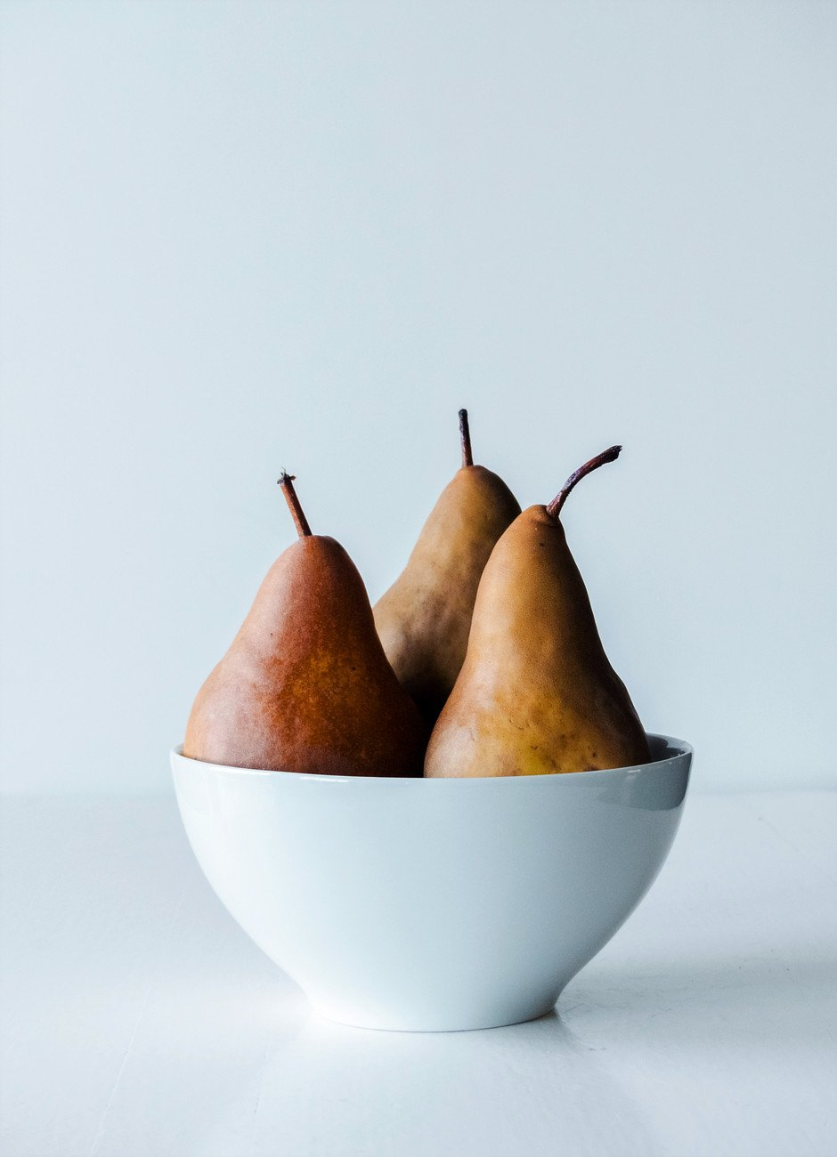 a straigh on image of three bosc pears in a white bowl against a white background.