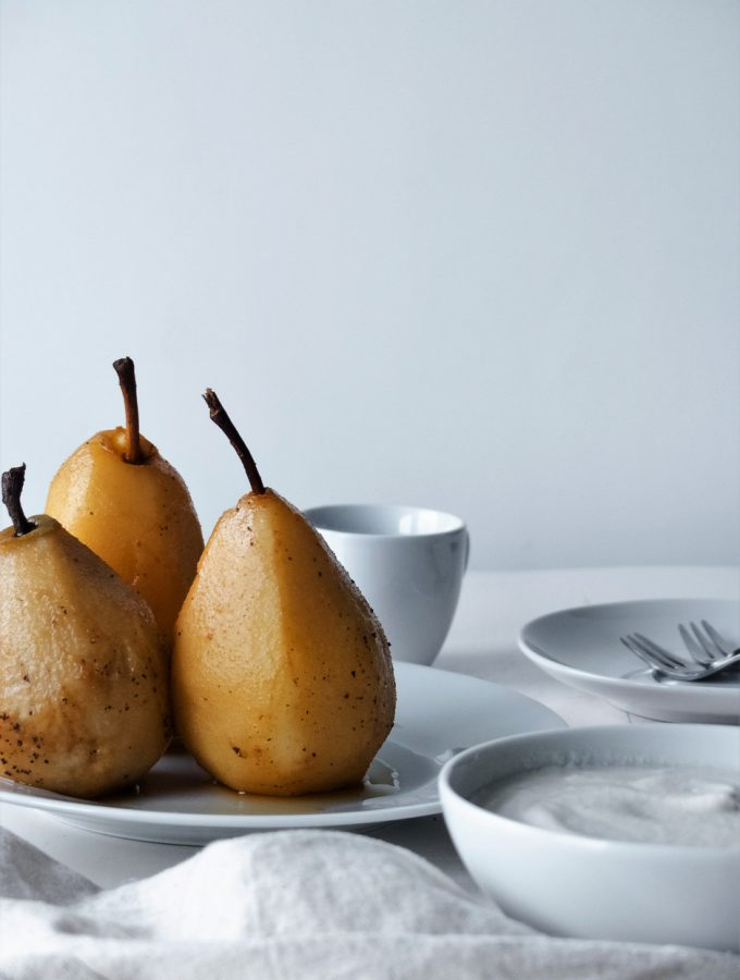 portrait of three poached pears on a plate with a bowl of cream, cutlery and small tea cup.