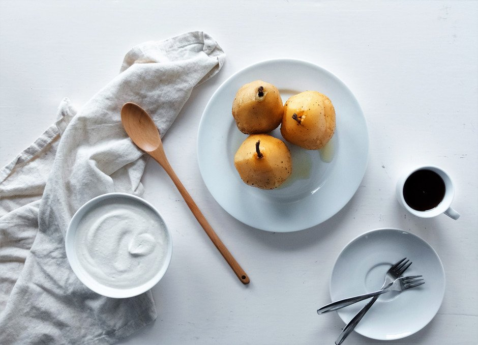 an overhead image of three chai poached pears sitting on a white plate, with a wooden spoon, white dishes and a white linen against a white surface.