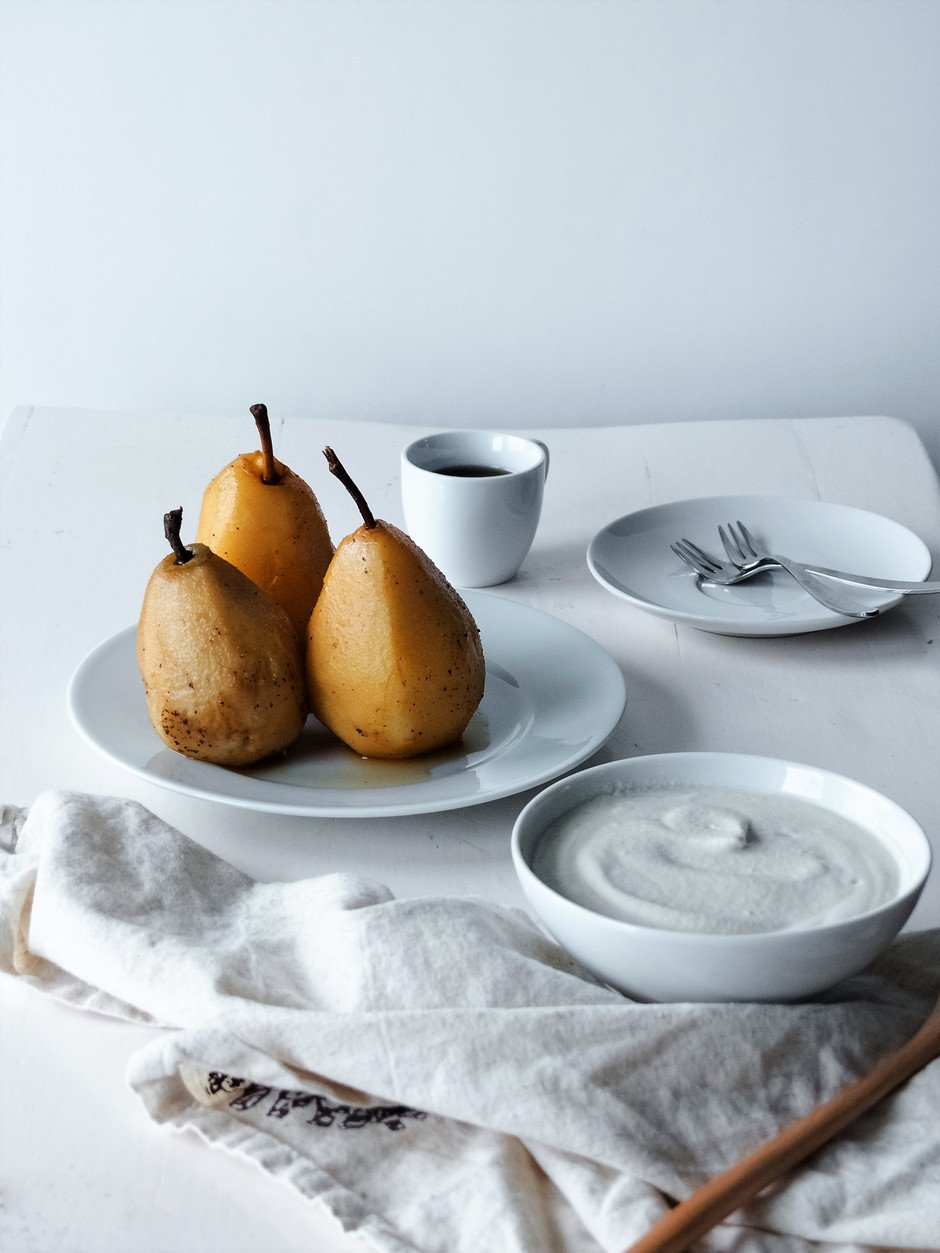 A straight on image of three Chai Poached Pears sitting on a white plate with white dishes off to the side.