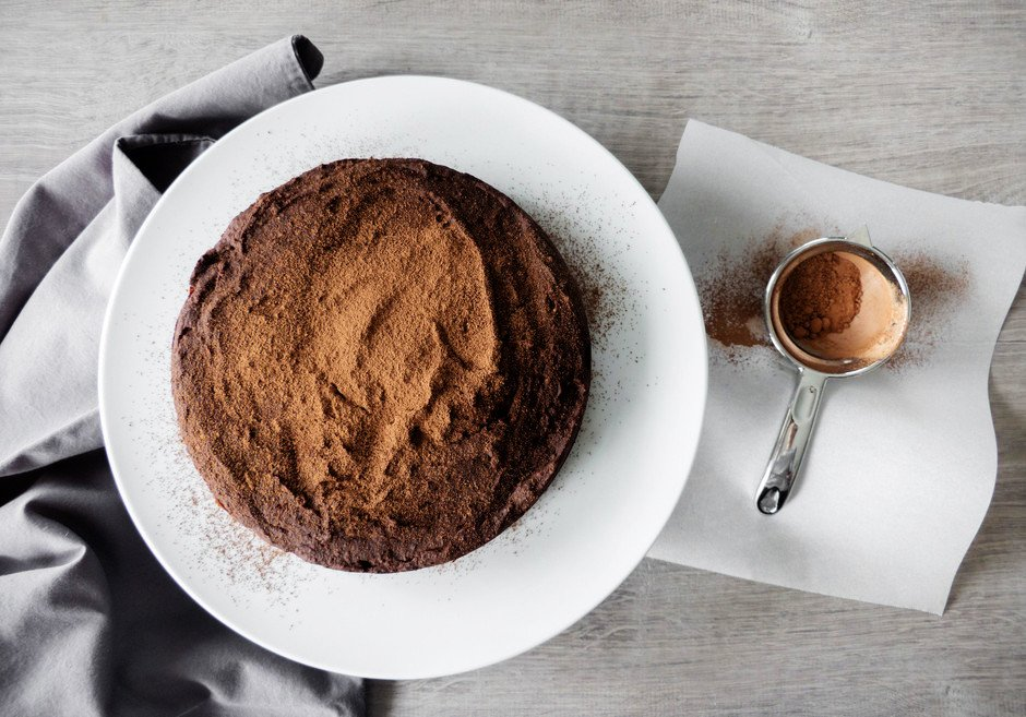 An overhead image of a vegan chocolate almond torte on a white plate with a fine sieve filled with cocoa powder on the right.