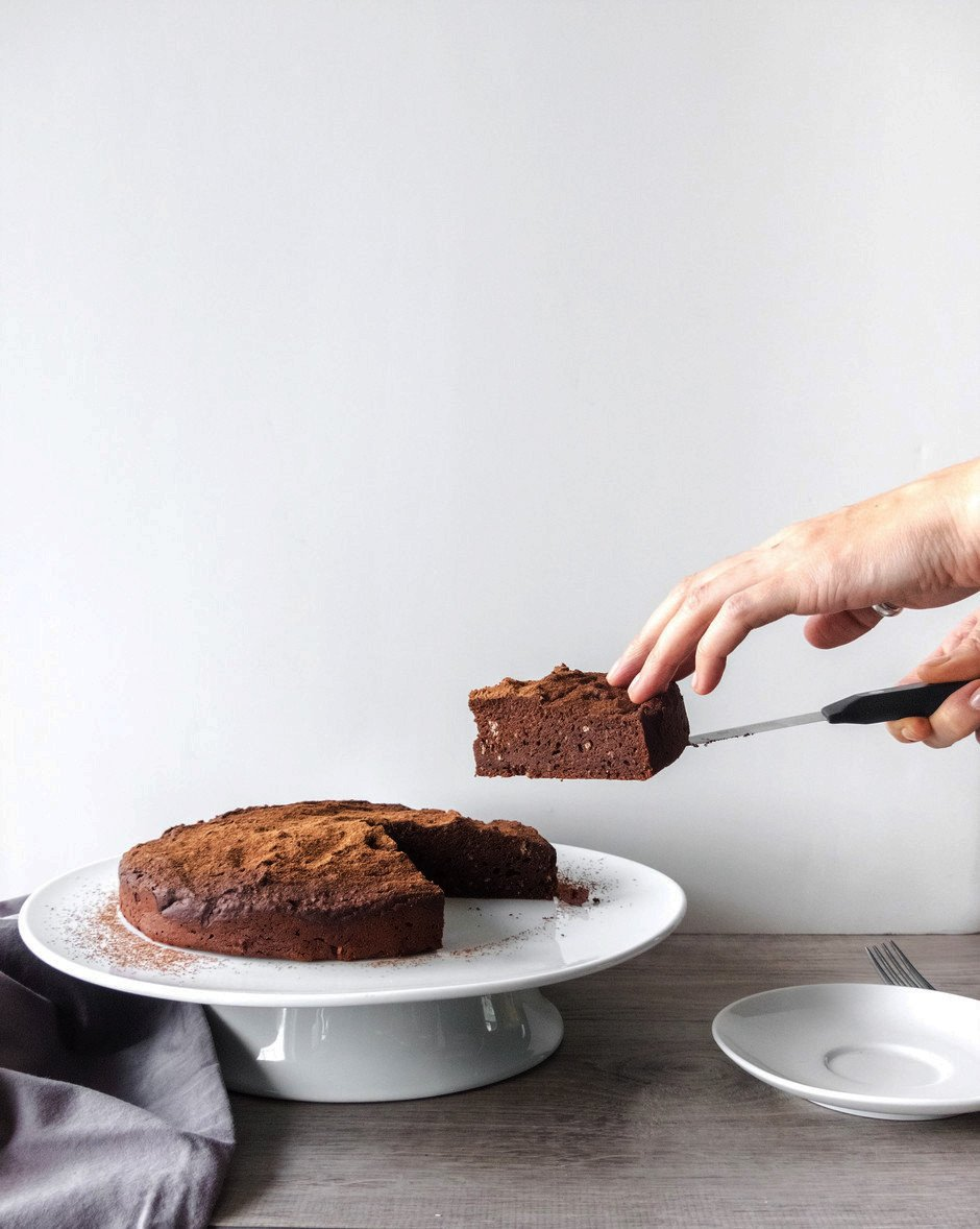 A head on image of a person removing a slice of a chocolate torte sitting on a white cake stand against a white background.