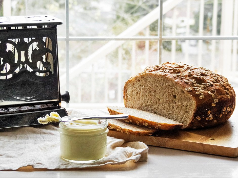head on image of a loaf of bread, a old fashioned toaster, and vegan butter in a jar.