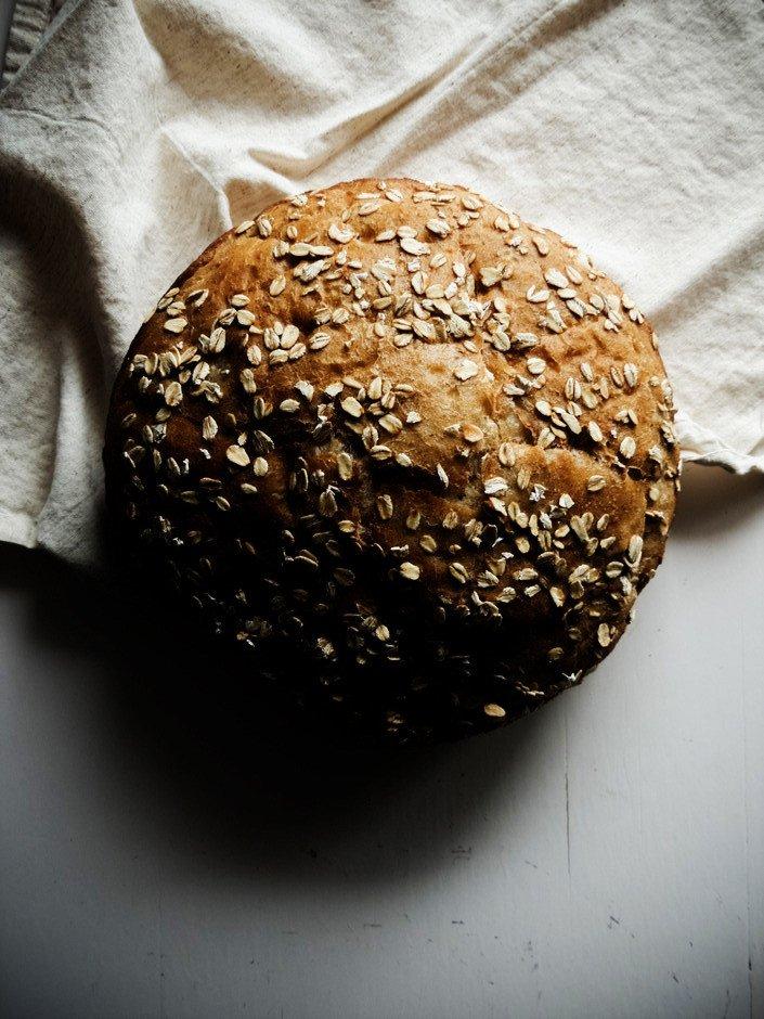 overhead image of no knead maple oat spelt bread sitting on a linen towel.