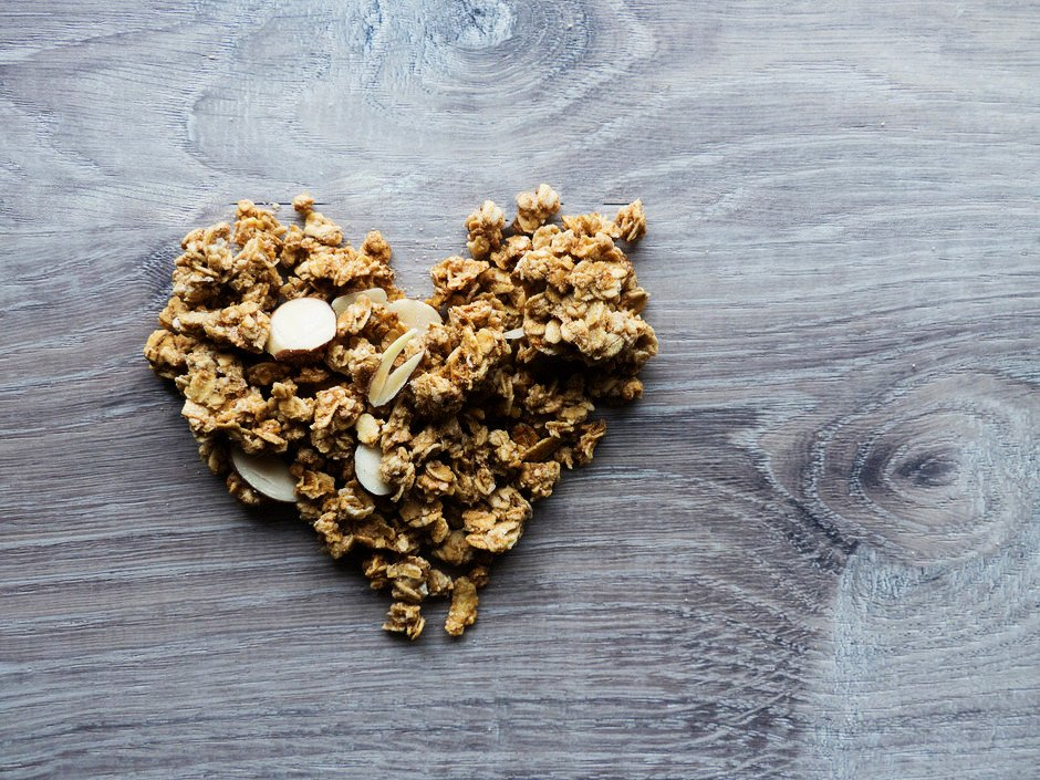 an overhead close up of granola shaped into a heart.