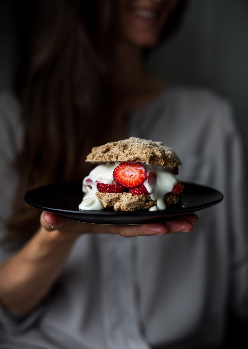 a person holding a strawberry shortcake on a black plate.