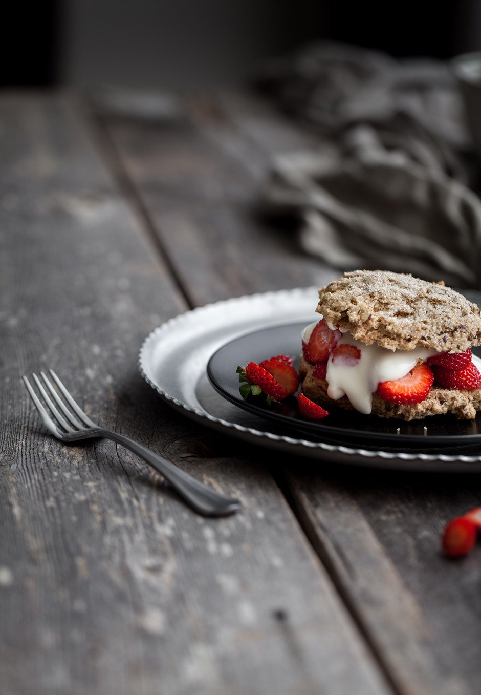portrait view of a vegan strawberry shortcake on a black plate with a fork on a wood surface.
