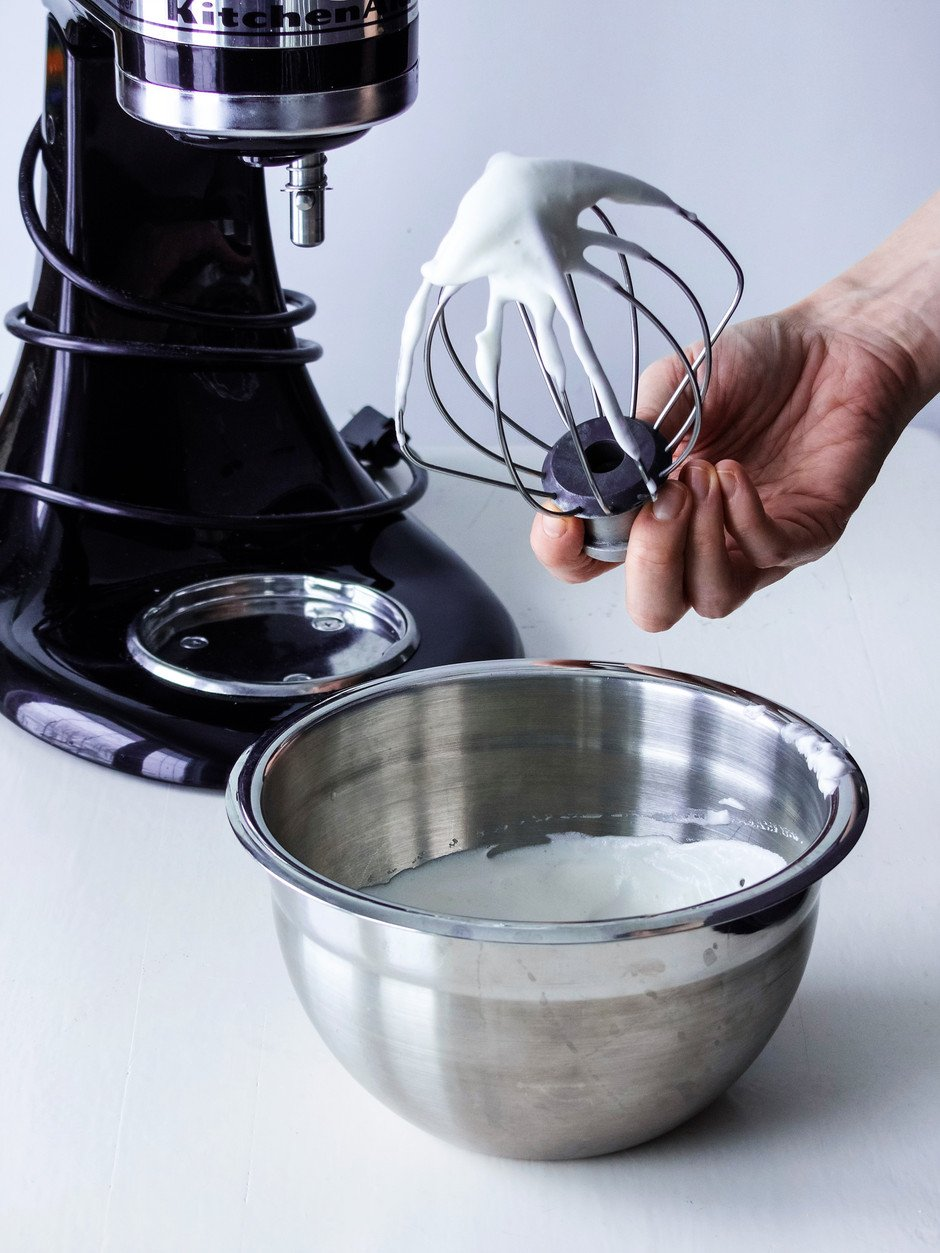 aquafaba in a bowl next to a stand mixer with a baker holding the whisk attachment.