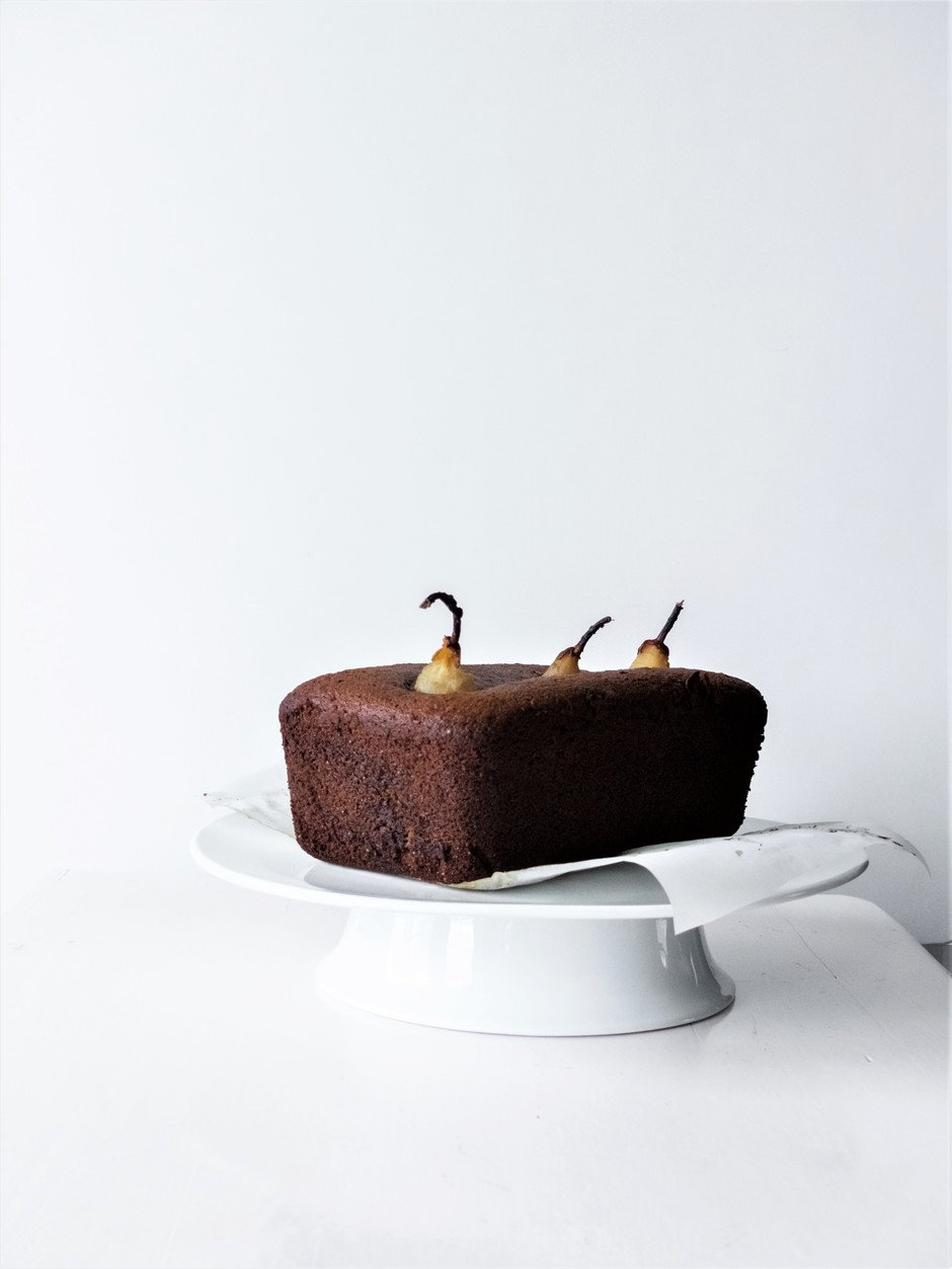 A head on image of a gingerbread loaf cake on a white cake stand.