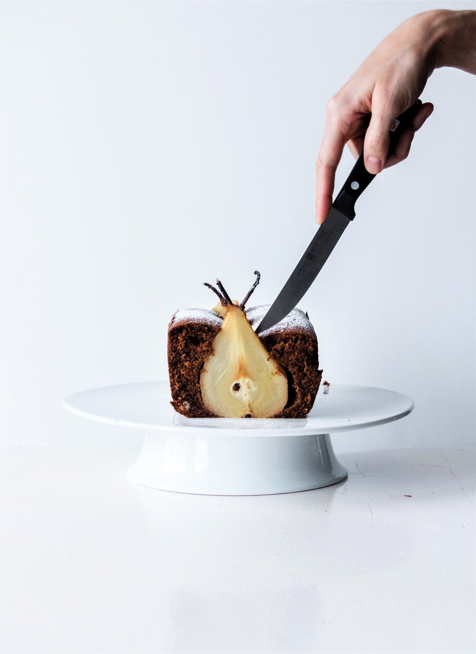 a head on image of a person cutting a slice of gingerbread loaf.
