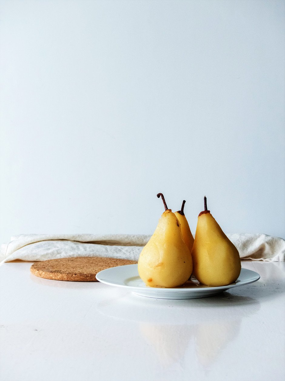 a straight on image of three poached pears sitting on a white plate against a white background.