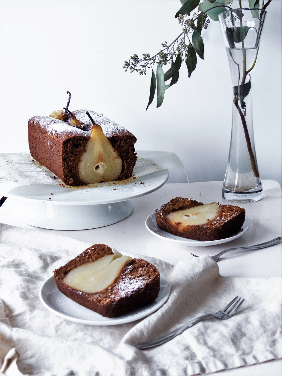 a head on image two slices of cake with a cake and evergreens in the background.